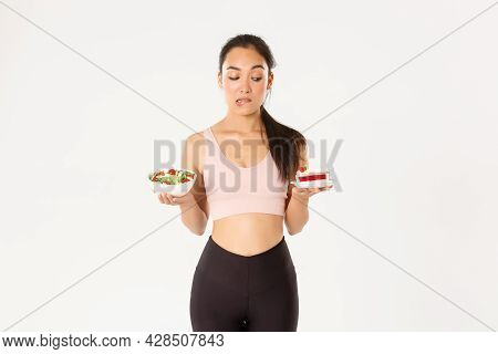 Active Lifestyle, Fitness And Wellbeing Concept. Portrait Of Indecisive And Tempting Cute Asian Girl
