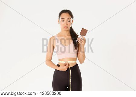 Sport, Wellbeing And Active Lifestyle Concept. Thoughtful And Indecisive Asian Girl Looking Gloomy O