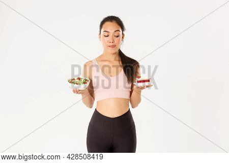 Active Lifestyle, Fitness And Wellbeing Concept. Portrait Of Tempting Cute Asian Girl Trying Resist