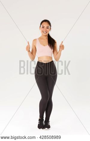 Full Length Of Satisfied Smiling, Cute Asian Fitness Girl, Sportswoman In Active Wear Showing Thumbs