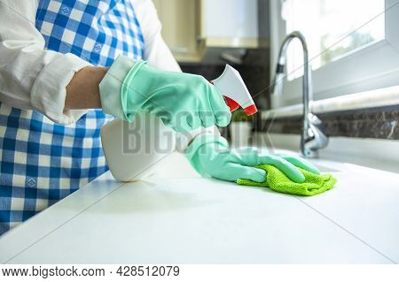 Unrecognizable Woman Cleaning Kitchen Counter With Rag And Spray Cleaner