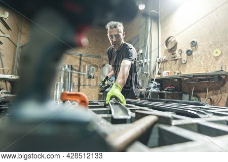 Worker Using Electric Wheel Grinding On Steel Structure In Factory
