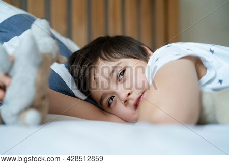 Close Up Face Happy Little Boy Waking Up In The Morning With Big Smile, Kid Lying In Bed Playing Wit