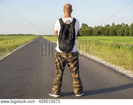 A Man With A Backpack Is Standing On An Asphalt Road And Looks Ahead With Folded Hands. Rear View. T