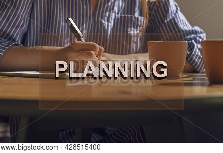 Planning Concept. Writing Notes, Plans In Notebook On Wooden Table With Coffee Cup.