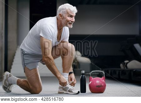 Handsome gray haired senior man with kettlebell weight. Sport and health care concept