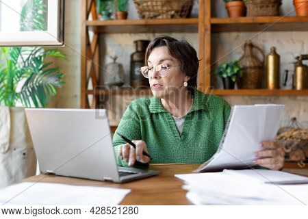 A Mature Woman While Filling Out Documents. She Uses An Online Tutorial To Fill In The Documentation