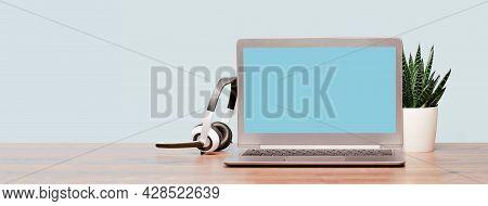 Laptop With Wireless Headphones On Wooden Desk