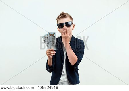 A Rich Boy On A Light Background Holds A Bundle Of Dollars In His Hands. Financial Education, Young