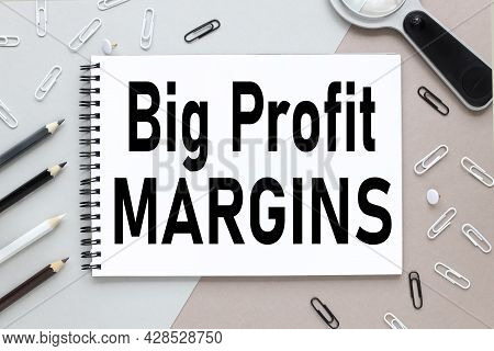 Big Profit Margins. Notepad On A Background Of Different Colors. Brown, Gray. Paper Clips Black And