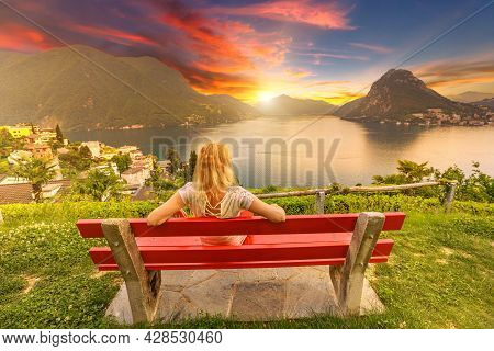 Woman On Top Of Lugano City By Lugano Lake In Switzerland. Red Bench At Lookout With Aerial View Fro