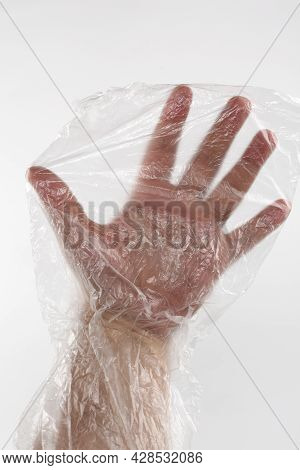 Male Hand In Plastic Wrap. Man's Hand In A Plastic Bag. Male Hand Inside A Transparente Wrap Bag.