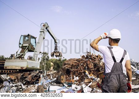 Junkyard Worker Supervisor Looking At Industrial Crane Machine Lifting Metal Parts For Recycling.