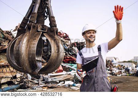 Junkyard Worker Waving To The Crane Operator To Start Lifting Scrap Metal Parts.