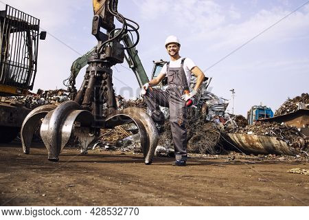 Portrait Of Junkyard Worker Standing By Hydraulic Industrial Machine With Claw Attachment Used For L