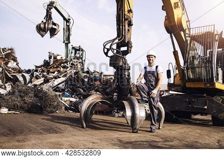 Portrait Of Junkyard Worker With Hardhat Standing Next To Hydraulic Industrial Machine With Claw Att