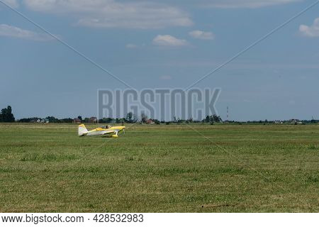 Plane Flying In The Sky Over The Airfield. Taking Off On The Aerodrome. Small Aviation Extreme Sport