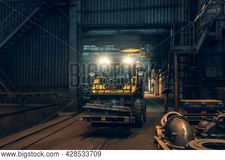 Small Yellow Loading Tractor Or Mower At Work In Metallurgical Factory Workshop.