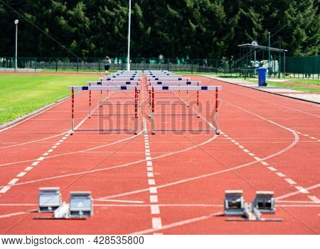 Hurdle On The Sprint Lane With Starting Blocks Against Blurry Background. Stadium With Two Hurdles T