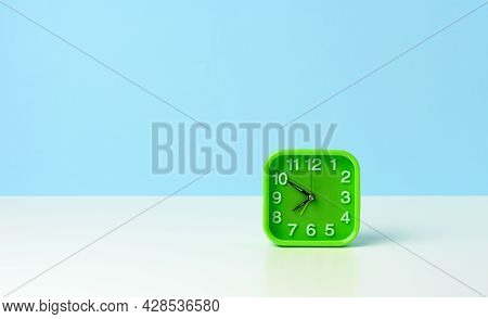 Square Green Clock With White Numbers On A White Table, Ten Minutes To Eight In The Morning, Morning