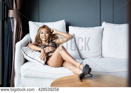 Asian Girl In Black Transparent Lingerie Lying On Sofa With Legs On The Table. Smiling