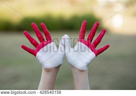 Child Girl Show Hands Painted In Indonesia And Monaco Flag Colors. Indonesian Patriotism Concept. In