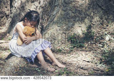 Sad Girl Hugging Teddy Bear Sitting Under Tree Sadness Alone In Green Park. Lonely Girl Feeling Sad