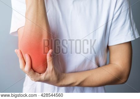 Young Adult Female With Her Muscle Pain On Gray Background. Woman Having Elbow Ache Due To Lateral E