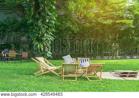 Many Deck Chairs And Pillows With Wooden Table In The Courtyard Is Surrounded By Shady Green Grass.