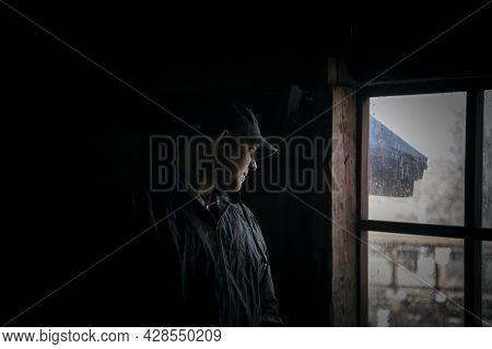 Silhouette Of A Suspicious Strange Man Looking Out The Window In A Scary Dark Attic Of An Old Abando