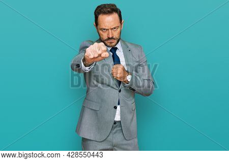 Middle age man wearing business clothes punching fist to fight, aggressive and angry attack, threat and violence