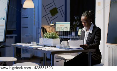 African American Businesswoman Sitting At Conference Table Drinking Coffee While Analyzing Financial