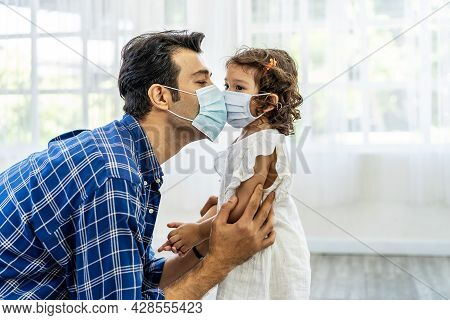 Caucasian Father Wearing Face Mask To Avoid Contagion  Kissing Daughter Through Medical Mask, During