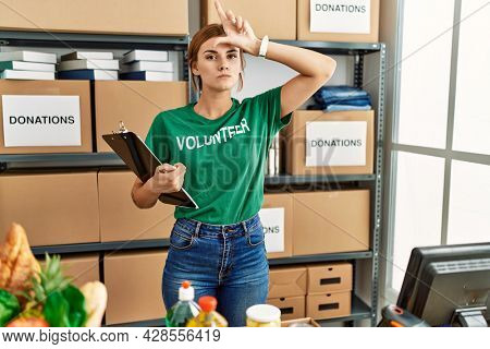 Young brunette woman wearing volunteer t shirt at donations stand making fun of people with fingers on forehead doing loser gesture mocking and insulting.