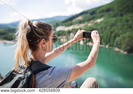 Mid Adult Woman Tourist On Hiking Trip On Summer Holiday, Taking Photograph With Smartphone.