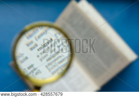 Word Emigrant Focus In A Magnifying Glass. Education, Foreign Language Learning, Search For Knowledg