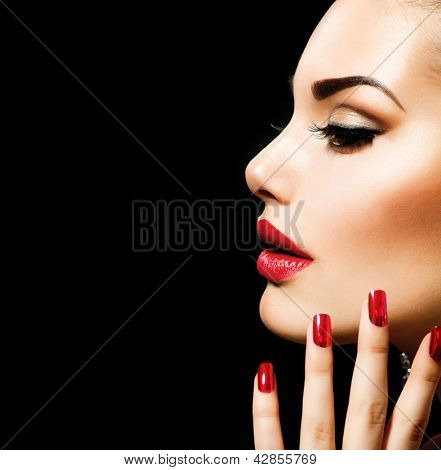Beauty Woman with Perfect Makeup. Beautiful Professional Holiday Make-up. Red Lips and Nails. Beauty Girl's Face isolated on Black background. Glamorous Woman