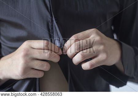 The Young Man Is Getting Dressed.the Concept Of Fashionable Clothing Is A Close-up Of A Man Getting