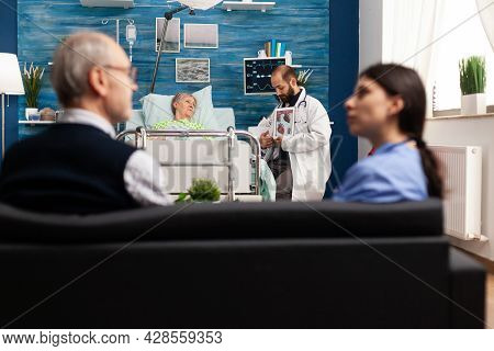 Support Doctor Worker Explaining Heart Radiography Discussing Medical Cardiogram With Retired Senior