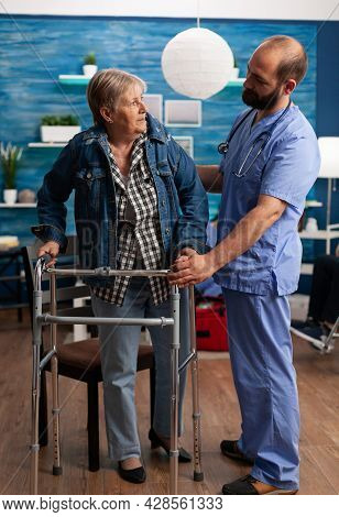Social Asisstant Man Worker Helping Pensioner Disabled Senior Woman During Recovery Therapy. Healthc