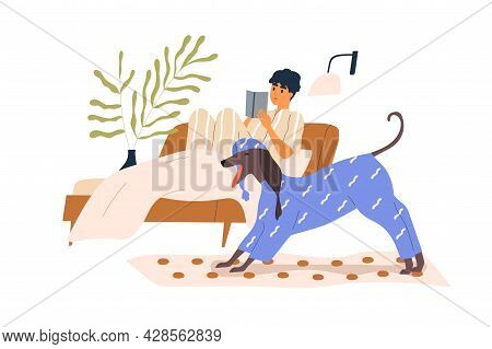 Cute Dog In Funny Pyjamas And Owner Resting In Bed And Reading Book In Cozy Home. Person And Doggy I