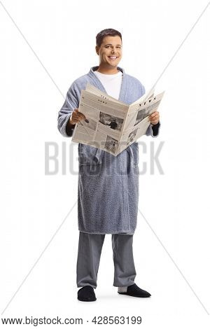 Man in pyjamas  and bathrobe standing and holding a newspaper isolated on white background