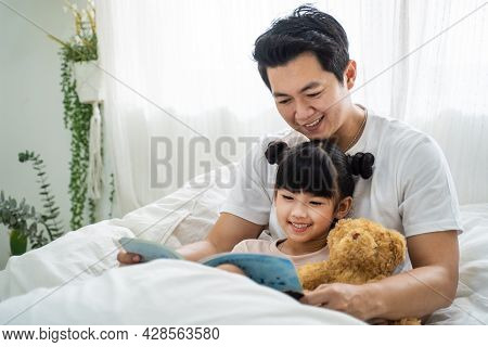 Asian Parent Spend Leisure Time With Kid Daughter In Bedroom At House. Happy Family, Loving Father T
