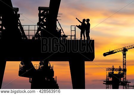 Silhouette Of Engineer And Worker Checking Project At Heavy Infrastructure Building Site Background,
