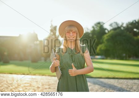 Cheerful Young Blonde Female University Or College Student With Laptop Wearing Green Dress And Hat I