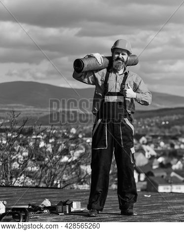 Roofer Repair Roof. Roof Installation. Man Hard Hat Work Outdoor Landscape Background. Building Hous