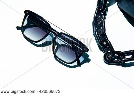 Black Eye Sunglasses And A Fashionable Handbag With Chain Isolated On White Background With Contrast