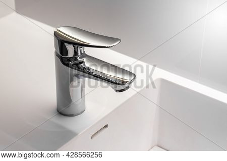 New Stainless Faucet On Clean Wash Basin Sink In Bathroom