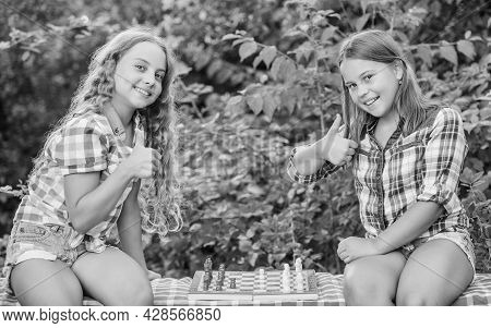Smart Children. Children Play Chess Outdoors Nature Background. Sport And Hobby Concept. Little Girl