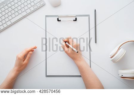 Woman Writing On Empty List In Notepad To Do List. Female Hands Do Sketching On Paper Tablet In Offi